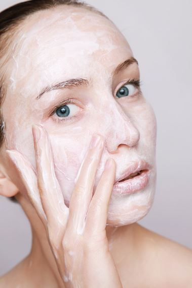 woman with skin care mask pointing to her under eye area