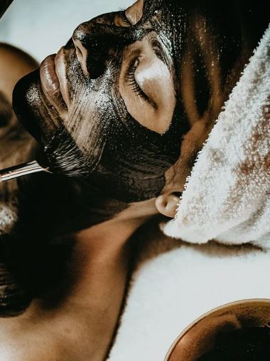 woman closing her eyes and resting with a black facial mask applied onto her face